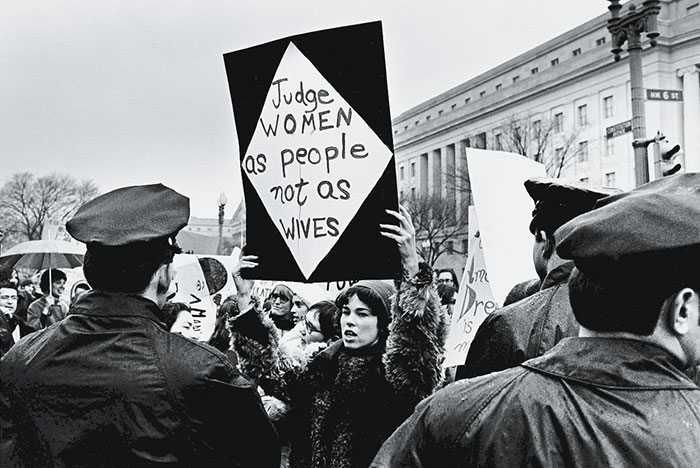 Marilyn Webb Holds Up A Sign As She Protests For Women's Rights In Front Of The Federal Trade Commission Headquarters While Policemen Look On During Richard Nixon's Inauguration Weekend, Washington, Dc, 18-21 January 1969