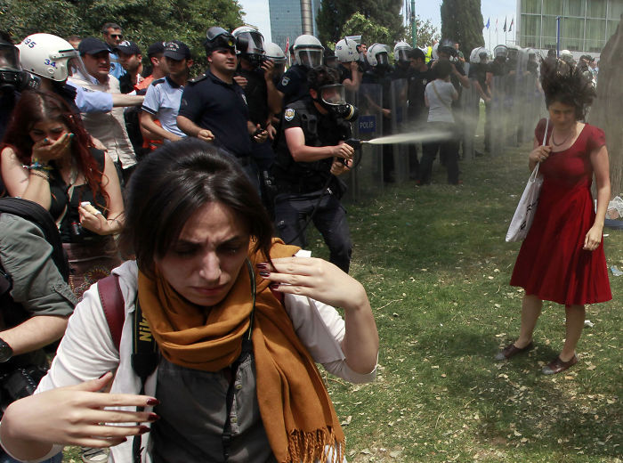 A Turkish Riot Policeman Uses Tear Gas As People Protest Against The Destruction Of Trees In A Park Brought About By A Pedestrian Project, In Taksim Square In Central Istanbul, 28 May 2013