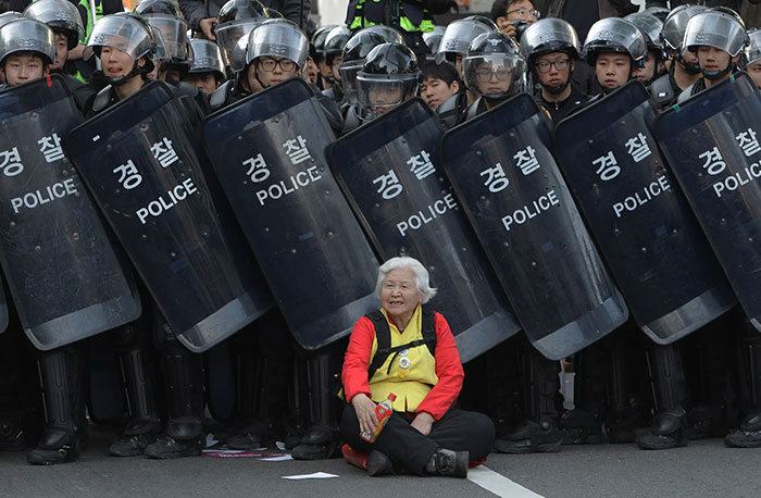 A Woman Sits In Front Of Riot Police Blocking The Road To Protect Protesters During The Anti-Government Protest In Seoul, South Korea, 24 April 2015