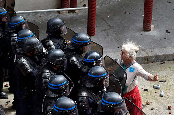 A Woman Stands In Front Of Police Officers As They Block Access To A Street During A Protest Against Proposed Labour Reforms In Paris, 14 June 2016