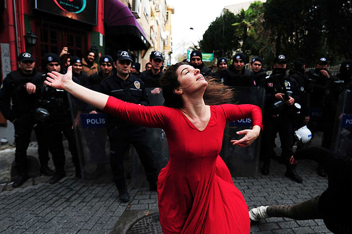 A Woman Dances In Front Of Riot Police During A Demonstration In The Kadikoy Neighborhood Of Istanbul Against The Eviction Of A Squatted Building, 9 December 2014