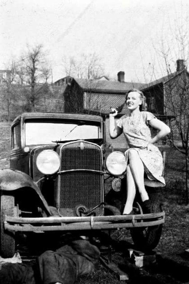 Моя великая тетя позирует, в то время как мой дедушка исправляет свой автомобиль, 1940-е годы