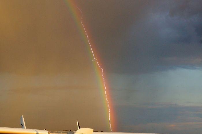 Rayo cayendo sobre un avión mientras volaba por un arco iris