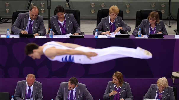 Two Rows Of Judges Ignore A Gymnast