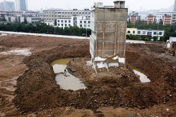 The Tenant Of This Apartment Building In Kunming, China, Has To Cross A Moat After The Contractors Dug A Ditch To Force The Last Family Out.