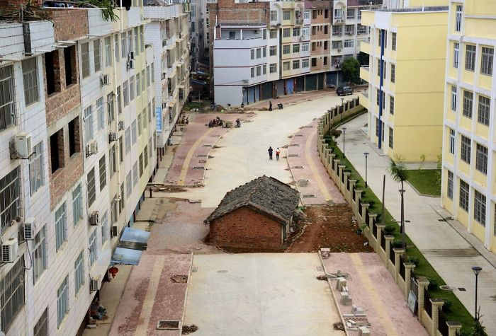A Nail House Sits In The Middle Of A Road Under Construction In Nanning, China, In April 2015. The Owner Of The House Didn't Reach An Agreement With The Local Authority About Compensation For The Demolition