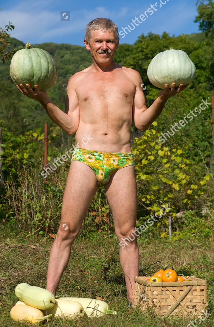 A Man Stands With Two Gourds In Hand, Wearing Nothing But A Speedo