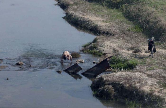 Man Bathing In A River Near His Town