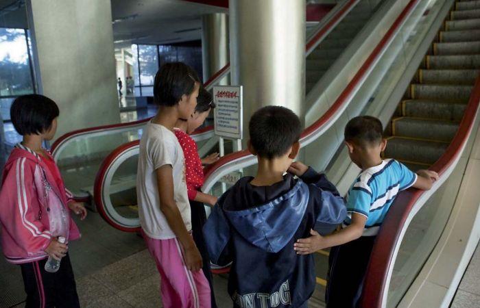 Niños del campo que tienen miedo de las escaleras automáticas porque nunca las habían visto