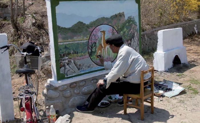 La prohibición más ridícula: este pintor oficial estaba haciendo un mural en Chilbo. Me gritaron al hacer la foto porque el mural no estaba terminado
