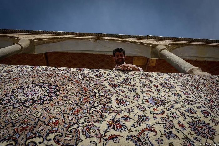 A Man Washes A Carpet In Isfahan Backyard Bazar