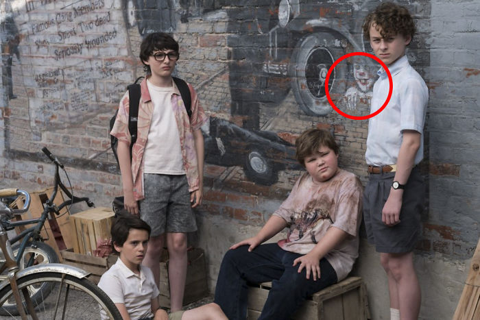 "In The Remake Of Stephen King's ""It,"" Pennywise The Clown Can Be Seen Hiding On One Of The Town's Murals"