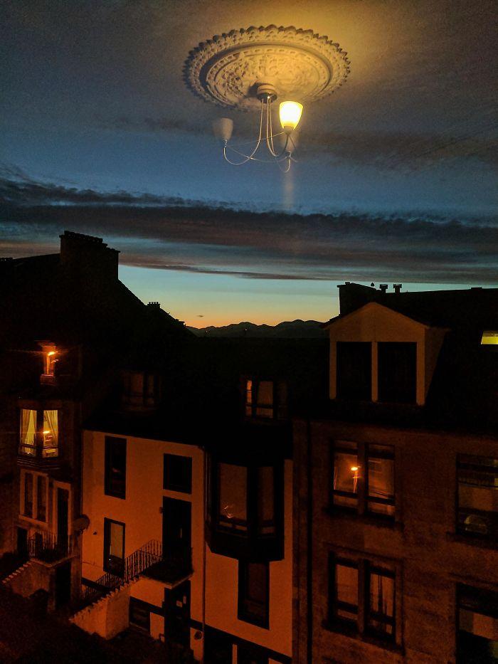 El reflejo de la lámpara en la ventana, parece que está flotando en el cielo
