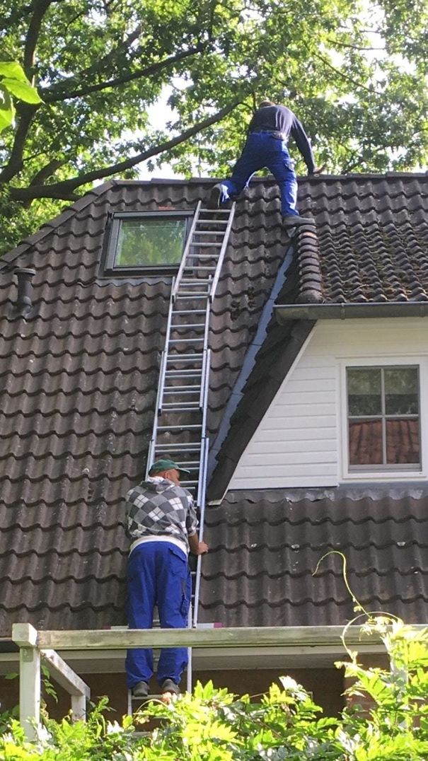 Standing On A Ladder That Is Held By A Ladder That Placed In A Gutter And Is Held By A Guy Who Is Standing On A Ladder