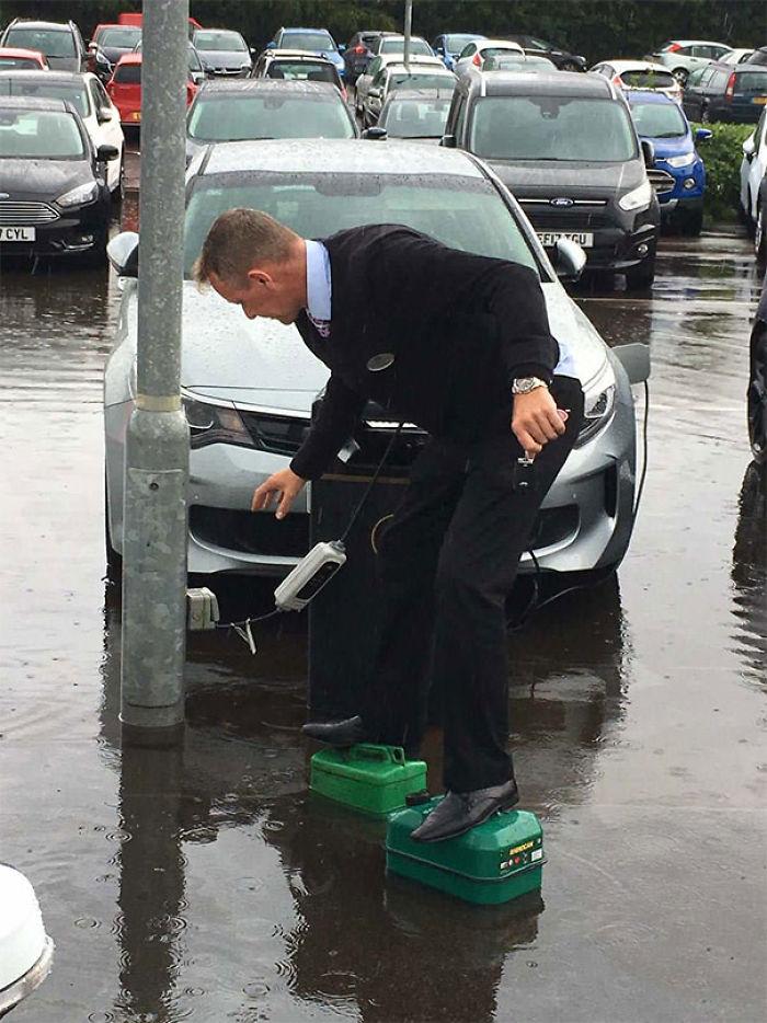 Desenchufando un coche eléctrico mientras usa latas de gasolina para evitar mojarse en la inundación.