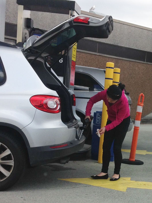 Woman At Station Using Gasoline To Clean Bumper