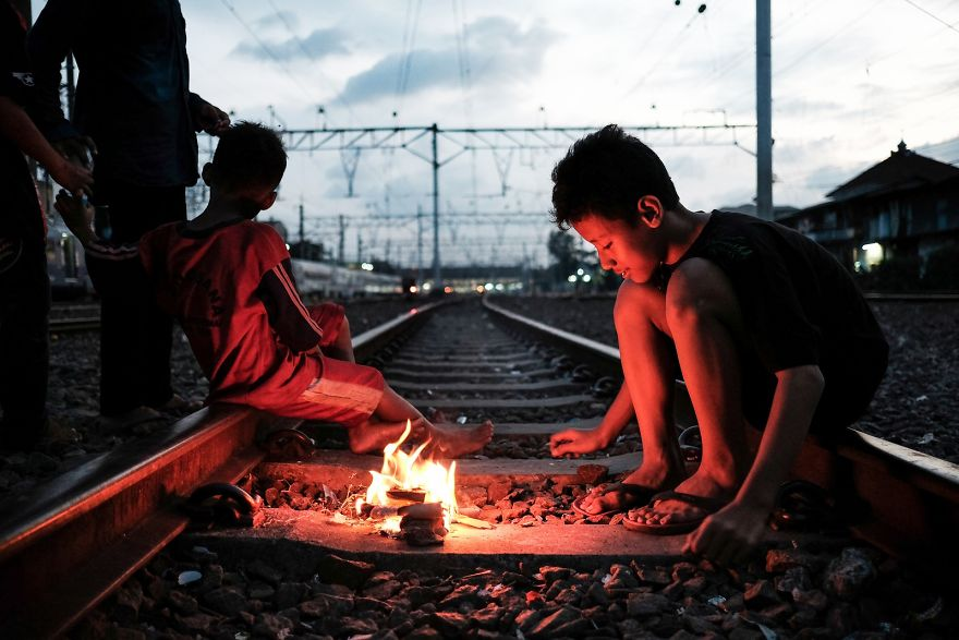 Kids Are Playing With Fire On An Active Railway Tracks In A Slum Area Next To Jakarta Kota Train Station. It Is The Only Playground They Have