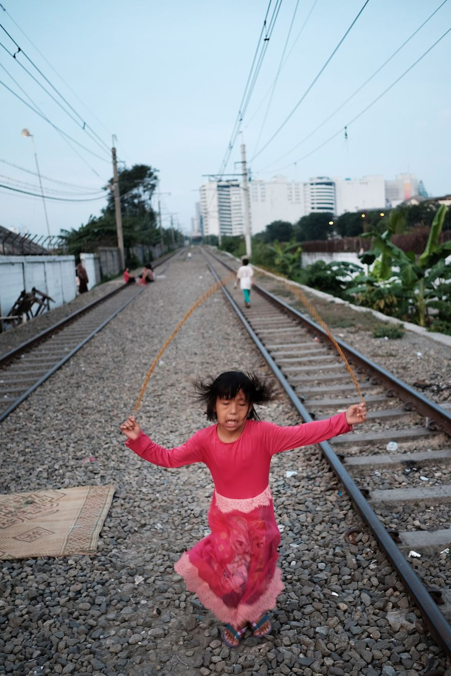 Girl Is Playing Next To Her Home On The Active Railway Tracks In One Of The Slums Of Jakarta