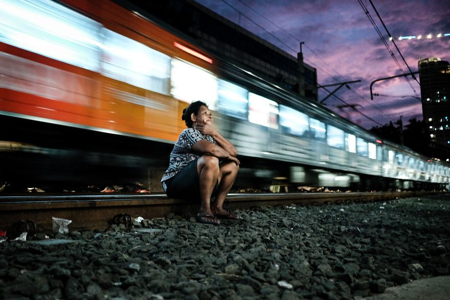 Women Is Sitting Comfortably On The Railway Tracks While Train Is Passing By Just A Couple Of Meters Behind Her