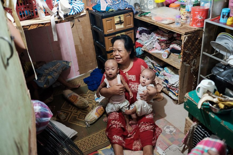 Woman With Her Grandchildren In Their Little Room. 5 People Are Living In This Small Room