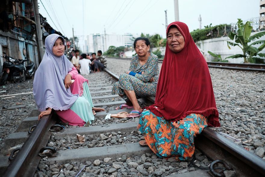 Women Sitting Comfortably On The Active Railway Tracks