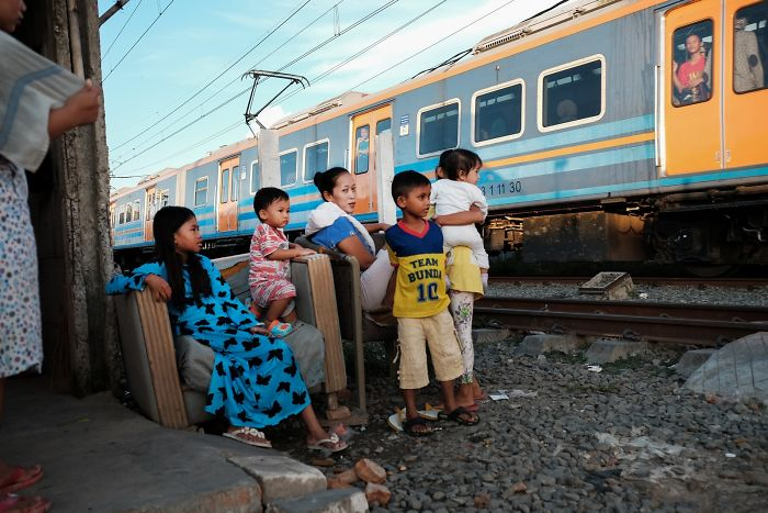 Family Is Watching The Train That Is Passing By Next To Their Home