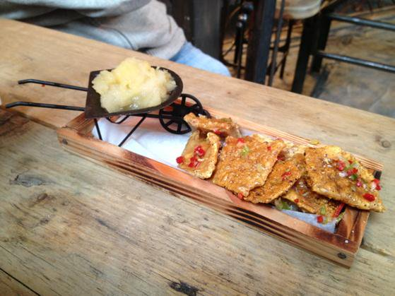 Pork Scratchings On A Plank, With A Mini Wheelbarrow Of Apple Sauce