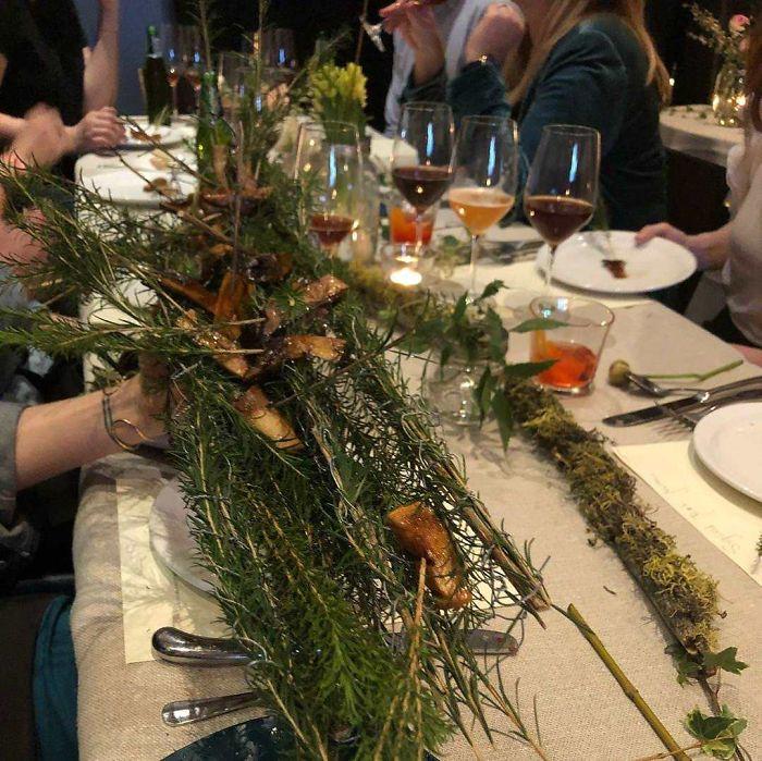 Ciruelas fermentadas servidas sobre ramas de pino