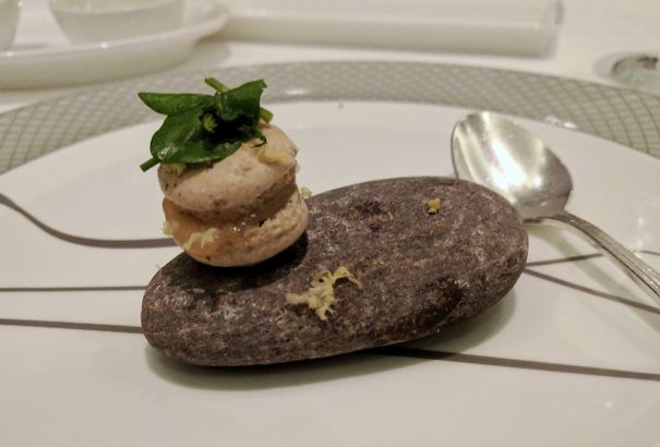 Single Mini Macaron Topped With Basil On A Rock