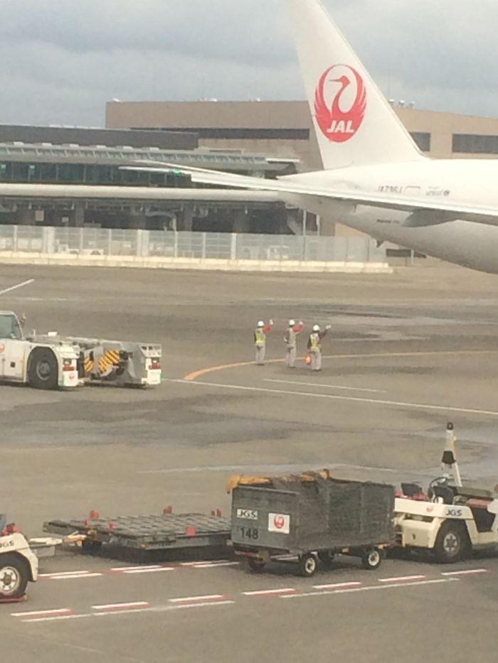 El personal de tierra japonés despide al avión que se va