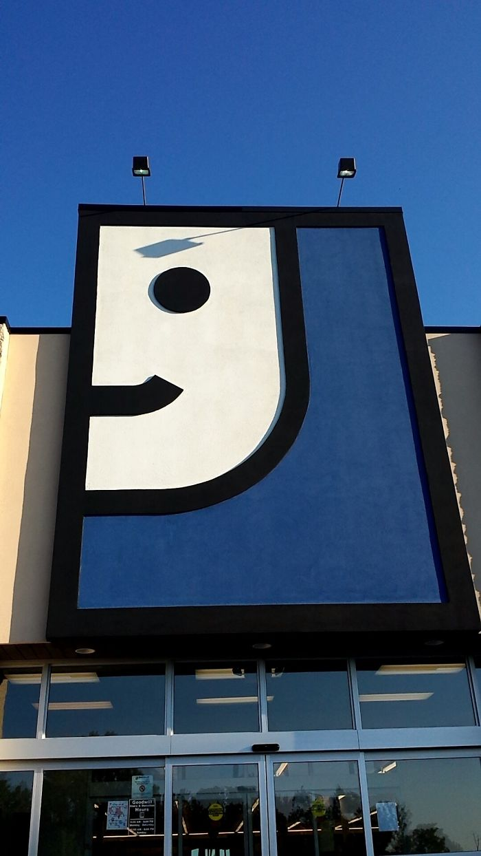 Shadow On Goodwill Sign Makes The Face Appear Menacing