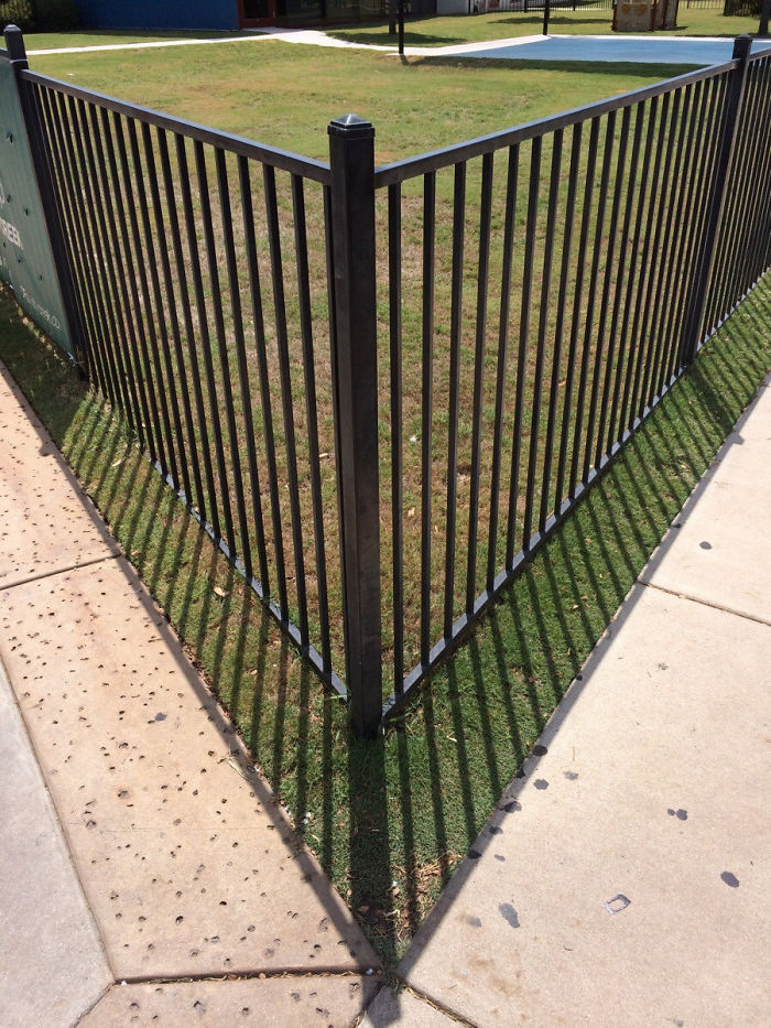 The Shadow From The Fence (Almost) Perfectly Lines Up With The Sidewalk