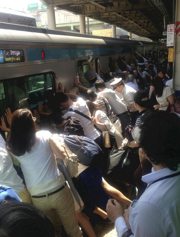 Viajeros empujando un vagón para salvar a una mujer que se cayó y quedó atrapada entre coche y andén