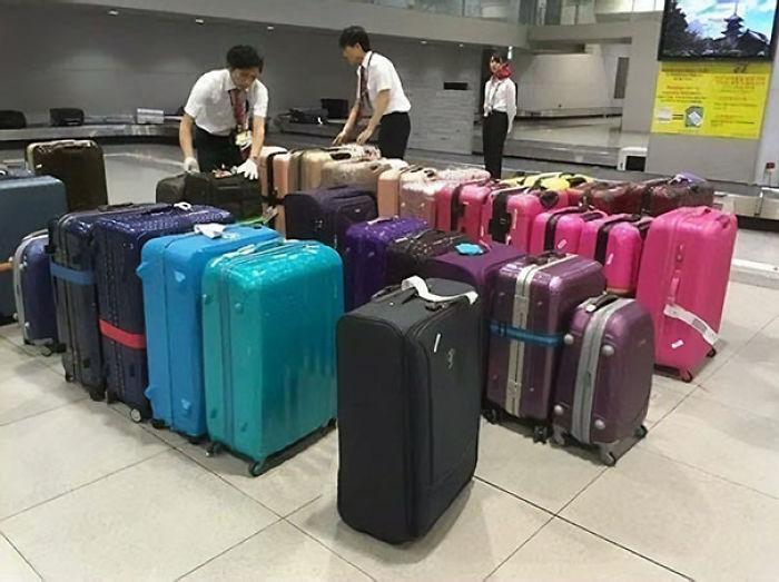 Personal del aeropuerto colocando el equipaje en la cinta por color