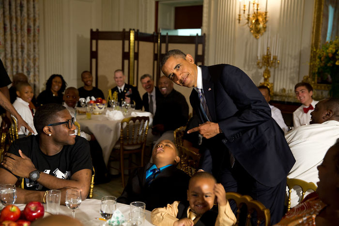 Obama posando para una foto con un chico que se ha quedado dormido en un evento social
