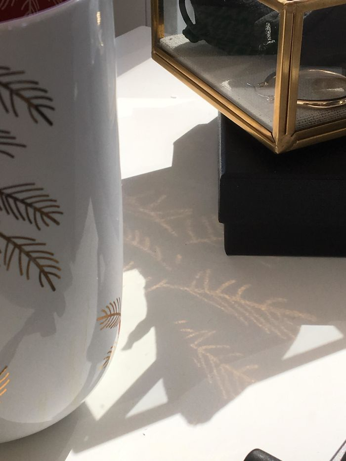 The Gold Designs On This Mug Being Reflected Onto Shadows