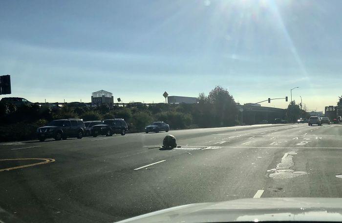Trabajador en una alcantarilla, en medio de una carretera de 4 carriles, sin conos, ni vallas, solo un chaleco naranja