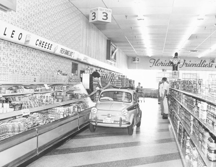Publix Supermarkets Showcased Their Wide Aisles And A Self-Service Dairy Case By Driving A Shopper Around A New Store In A Tiny Car, Circa 1957