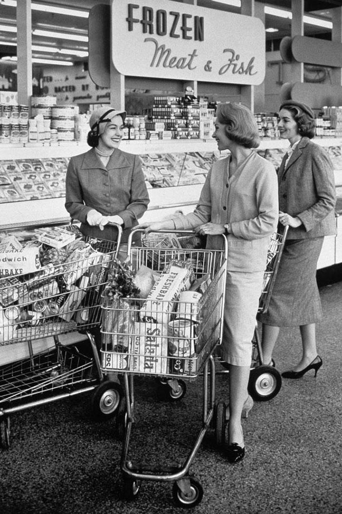 Tres mujeres hablando en el pasillo de alimentos congelados del supermercado, años 50
