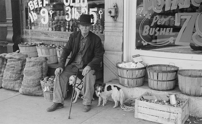 Man And Dogs In Front Of Grocery Store, Robinson, Illinois, 1940
