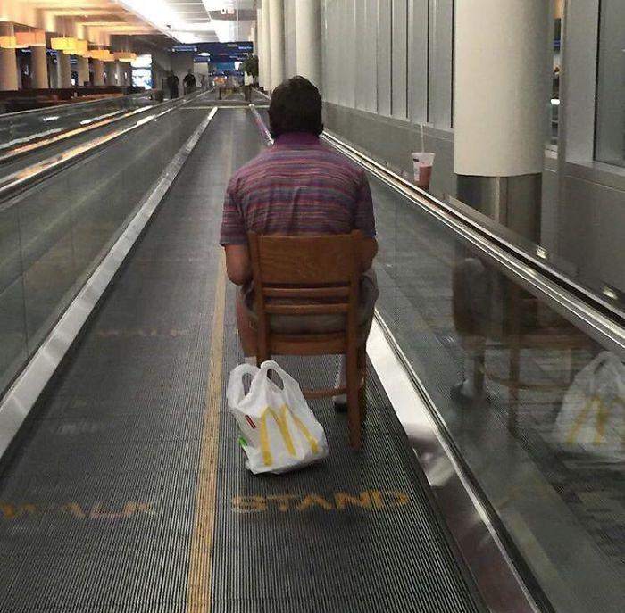 En el pasillo móvil del aeropuerto, sentado en su silla, comiendo hamburguesa y cazando pokemon