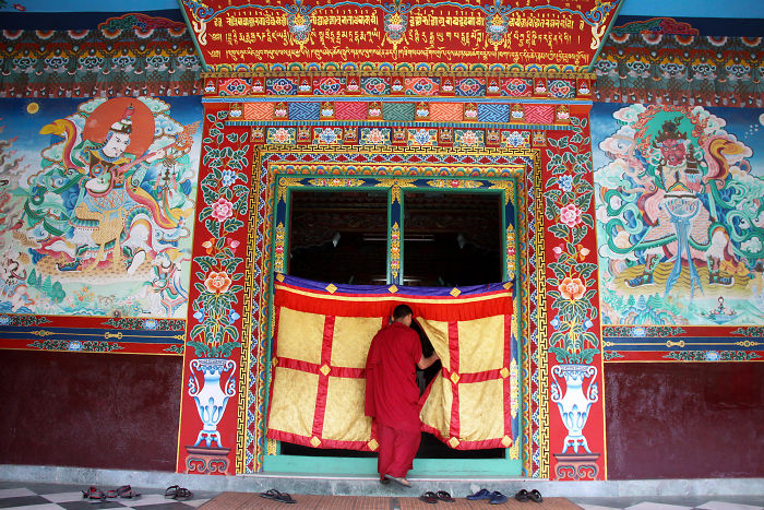 A Buddhist Monk Enters The Prayer Room Of Tharlam Monastery In Boudhanath, Nepal