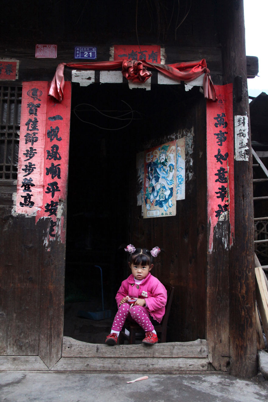 A Young Girl Is Posing At The Entrance Of Her House In Shiqiao, Guizhou Province, China
