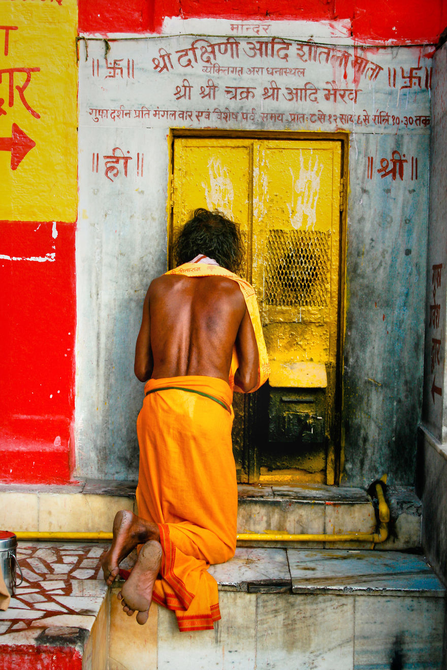 A Man Prays At The Door Of A Temple Of The Legendary City Varanasi, India