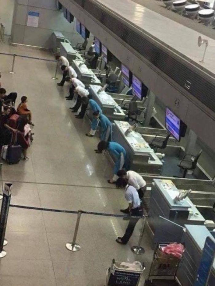 Un Vuelo Retrasado En Japón. Los Empleados De La Aerolínea Se Inclinan Ante Los Pasajeros Para Disculparse