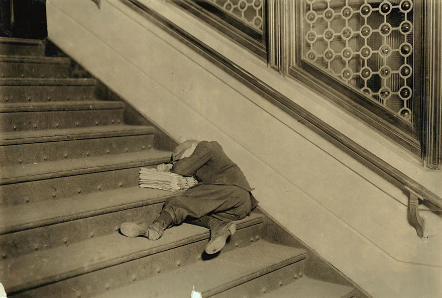 Newsboy Asleep On Stairs With Papers. Location: Jersey City, New Jersey