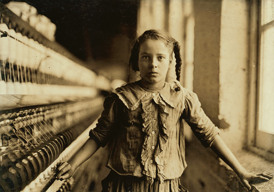 """One Of The Spinners In Whitnel Cotton Mfg. Co. N.c. She Was 51 Inches High. Had Been In Mill 1 Year. Some At Night. Runs 4 Sides, 48 Cents A Day. When Asked How Old, She Hesitated, Then Said """"I Don't Remember."""" Then Confidentially, """"I'm Not Old Enough To Work, But I Do Just The Same."""" Location: Whitnel, North Carolina"""