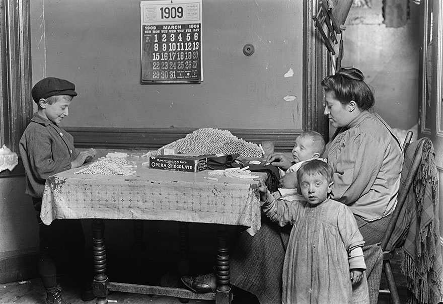 Widow & Boy Rolling Papers For Cigarettes In A Dirty N.y. Tenement. Location: New York, New York