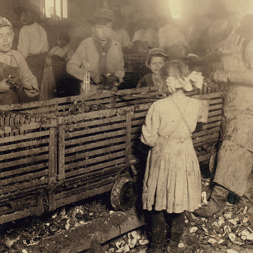 """Scene In Canning Factory Showing A 7-Year Old Girl Who Shucks 3 Pots Of Oysters A Day, And Works Regularly, And Her 6-Year Old Brother Who Helps Some. Mostly Negro Workers. The Boss Said """"We Keep Only Enough Whites So We Can Control The Negroes And Keep Them Agoing."""" Location: Bluffton, South Carolina"""
