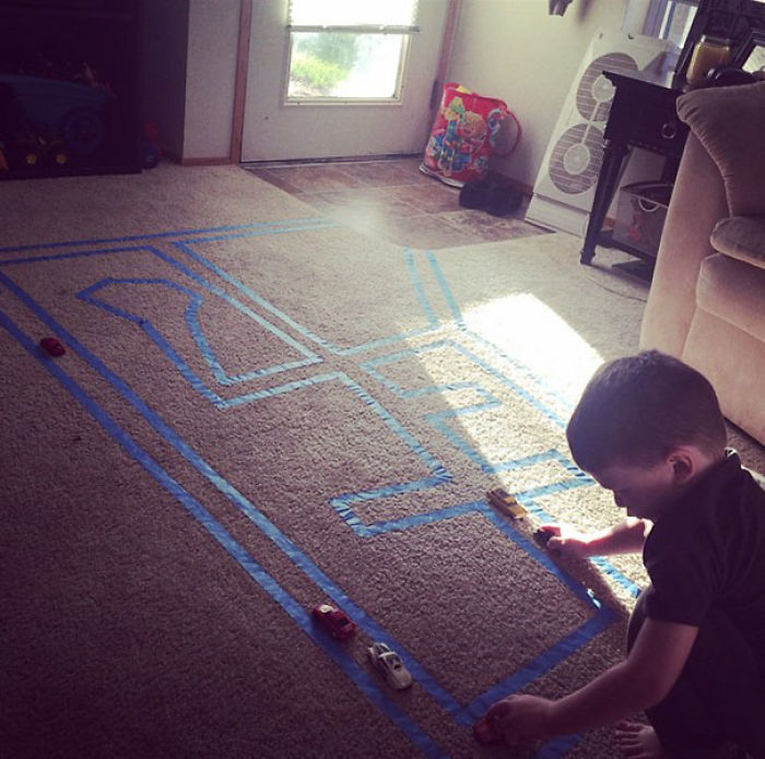 Pon cinta de pintor en la alfombra para que tu hijo juegue con cochecitos
